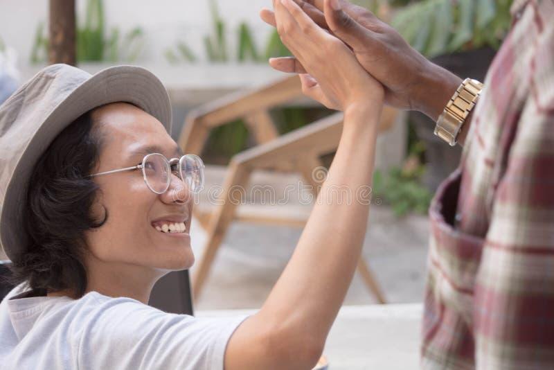Pain grillé asiatique de main d'homme avec un ami tout en tenant un comprimé ou un ordinateur portable, une secousse de main d'ho images stock