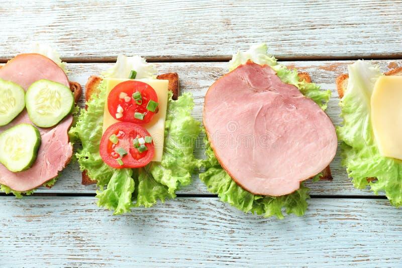 Pain grillé avec du jambon et des légumes sur la table en bois images stock