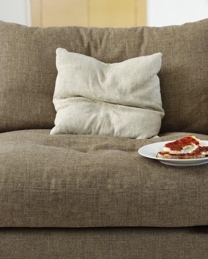 Pain grillé avec la confiture du plat sur le sofa image stock