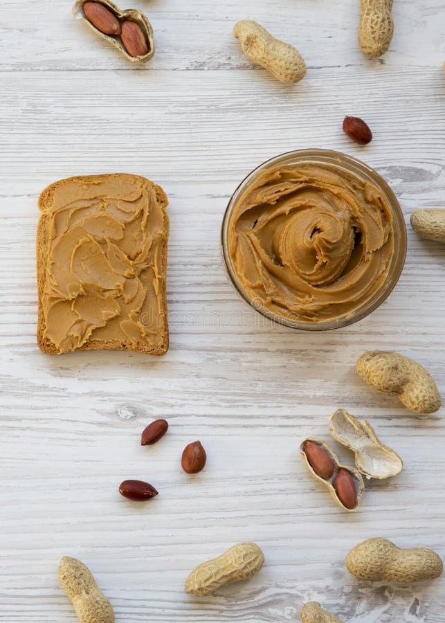 Pain grillé, bol de beurre d'arachide, arachides sur une table en bois blanche, vue supérieure D'en haut, configuration plate, aé photo libre de droits