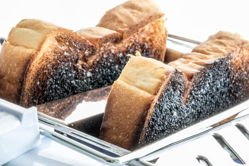Pain grillé brûlé dans un grille-pain photos stock