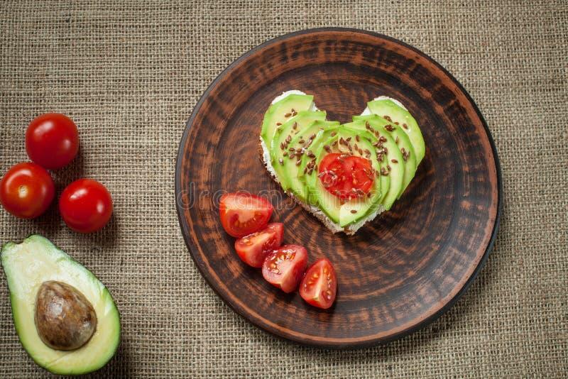 Pain grillé d'avocat avec la tomate sous forme de coeur photos libres de droits