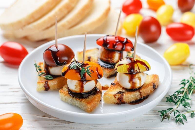 Pain grillé de pain avec la cerise de tomate, le fromage de mozzarella, le thym et balsamique images libres de droits
