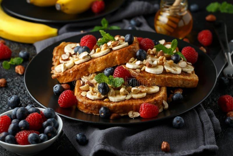 Pain grillé de cannelle français avec des myrtilles, des framboises, la banane, des écrous, la noisette et le miel images stock