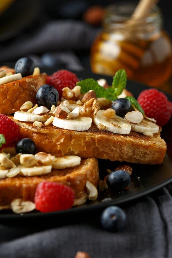 Pain grillé de cannelle français avec des myrtilles, des framboises, la banane, des écrous, la noisette et le miel photos stock