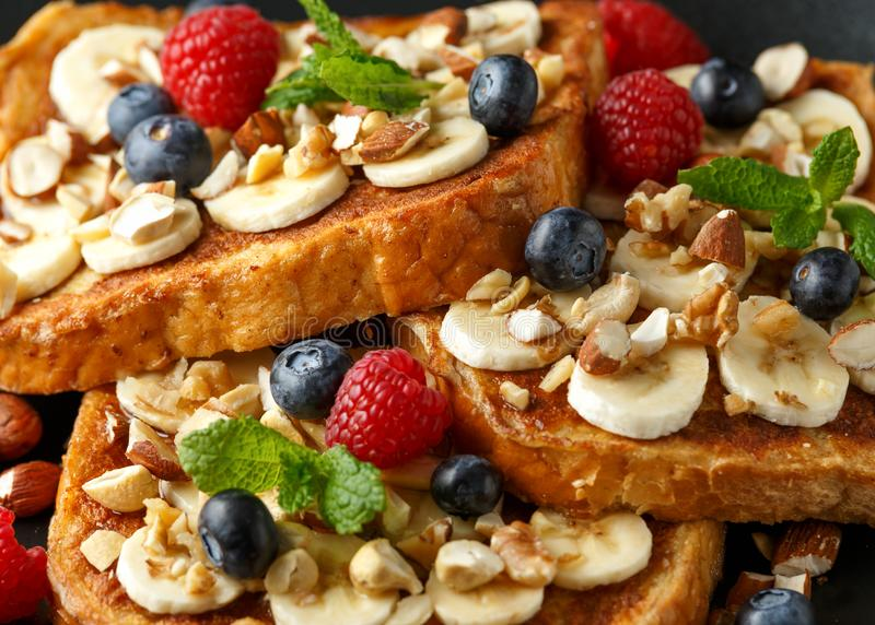 Pain grillé de cannelle français avec des myrtilles, des framboises, la banane, des écrous, la noisette et le miel photo libre de droits