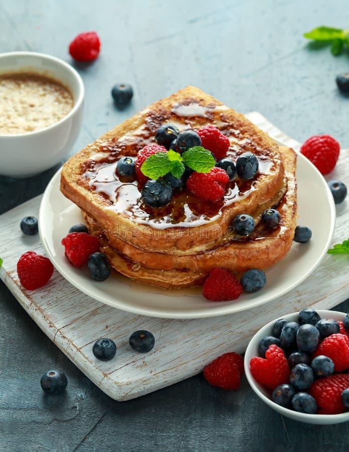 Pain grillé de cannelle français avec des myrtilles, des framboises, le sirop d'érable et le café Petit déjeuner de matin photographie stock