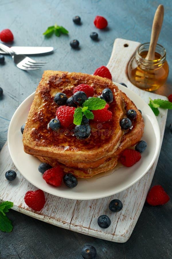 Pain grillé de cannelle français avec des myrtilles, des framboises, le sirop d'érable et le café Petit déjeuner de matin image libre de droits