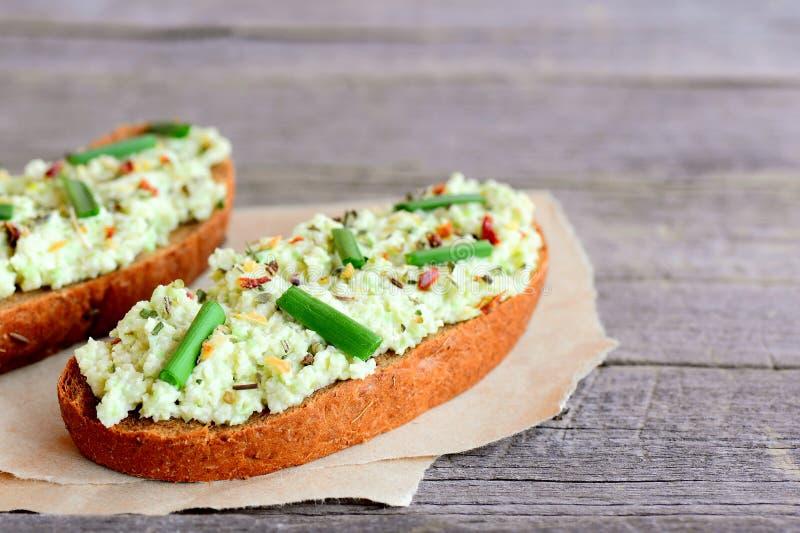 Pain grillé de pain de Rye avec le guacamole, l'oignon vert frais et les herbes sèches sur un papier et une vieille table en bois photographie stock