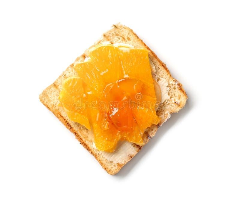Pain grillé doux savoureux avec du beurre, le miel et des morceaux d'orange sur le fond blanc photo stock