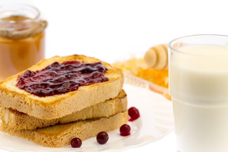 Pain grillé français frais avec du miel et la confiture d'un plat blanc avec des baies sur un fond blanc photographie stock libre de droits