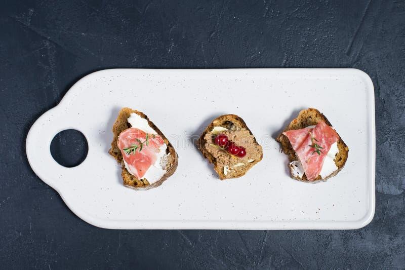 Pain grill? avec le p?t? de Parme, de salami et d'oie sur un hachoir blanc photographie stock libre de droits
