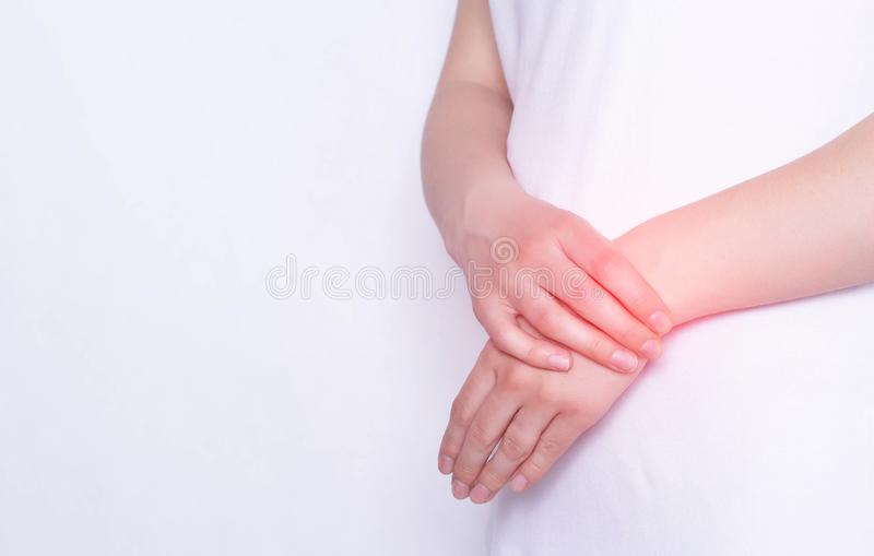 Pain and inflammation in the hand on the wrist of a girl, carpus, tendonitis and podagra, white background, copy space. Pain and inflammation in the hand on the stock photo