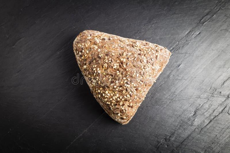 Pain intégral sous forme de triangle avec le lin oléagineux, l'avoine et les graines de sésame photos libres de droits