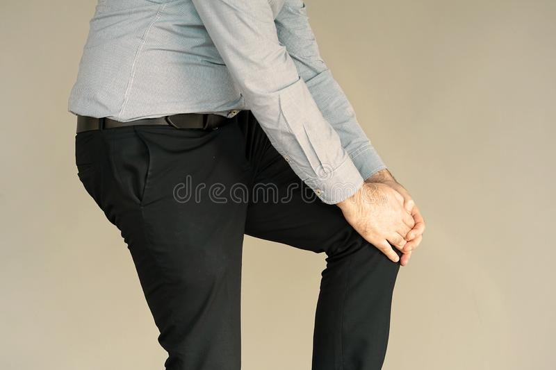 Businessman Pain in the knees of a man. Pain In Knee. Close-up Businessman Leg With Painful Kneeson . Man Feeling Joint Pain, Having Health Issues And Touching royalty free stock photo