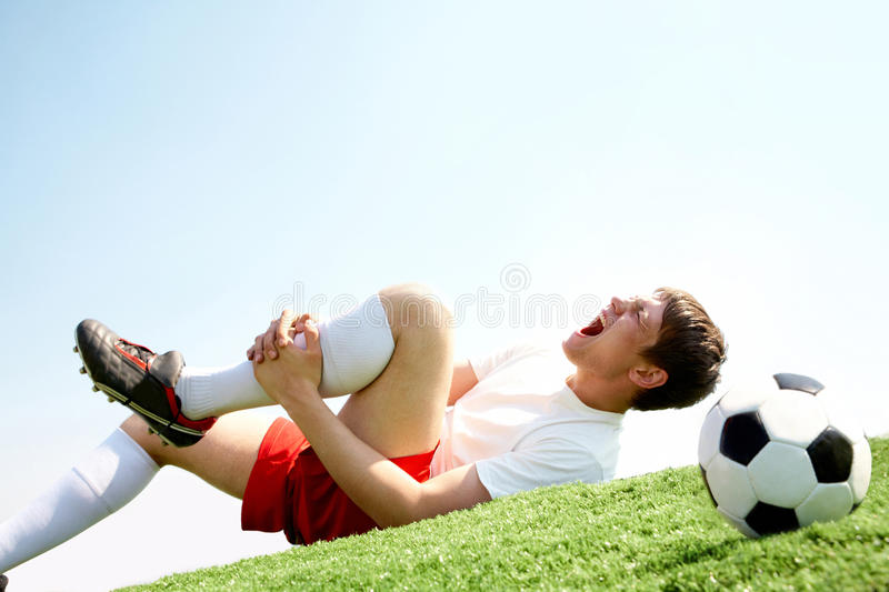 Pain in leg. Image of soccer player lying down and shouting in pain stock image