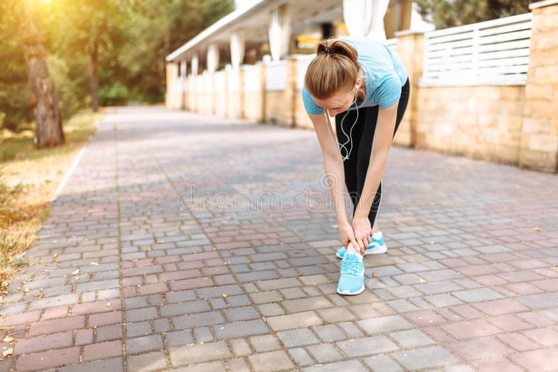 Pain in the leg of the girl after a sports run, morning training, stretching of the leg. Pain in the leg of the girl after a sports run, morning training royalty free stock images