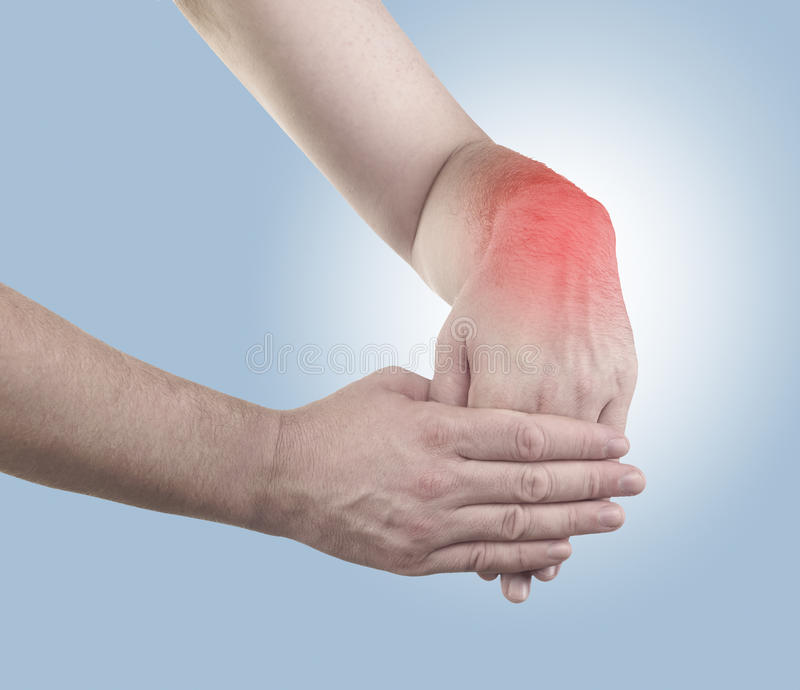 Pain in a man wrist. Male holding hand to spot of wrist pain royalty free stock photography