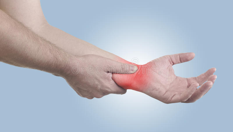 Pain in a man wrist. Male holding hand to spot of wrist pain royalty free stock image