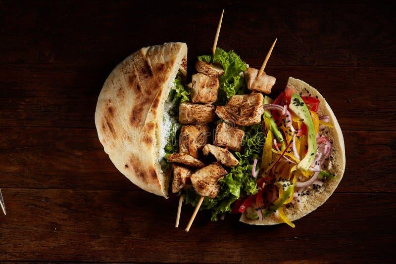 Pain pita bourré du poulet, des légumes et du chiche-kebab sur le fond en bois, vue supérieure, foyer sélectif image stock