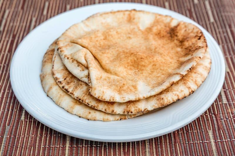 Pain pita de Brown d'un plat blanc photos libres de droits