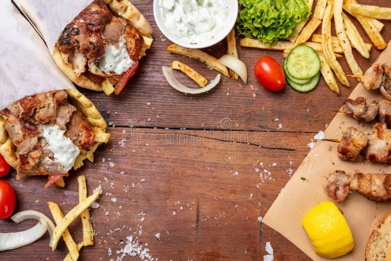Pain pita de compas gyroscopique, shawarma, souvlaki Deux enveloppes de pain pita et brochettes de viande sur la table en bois image libre de droits