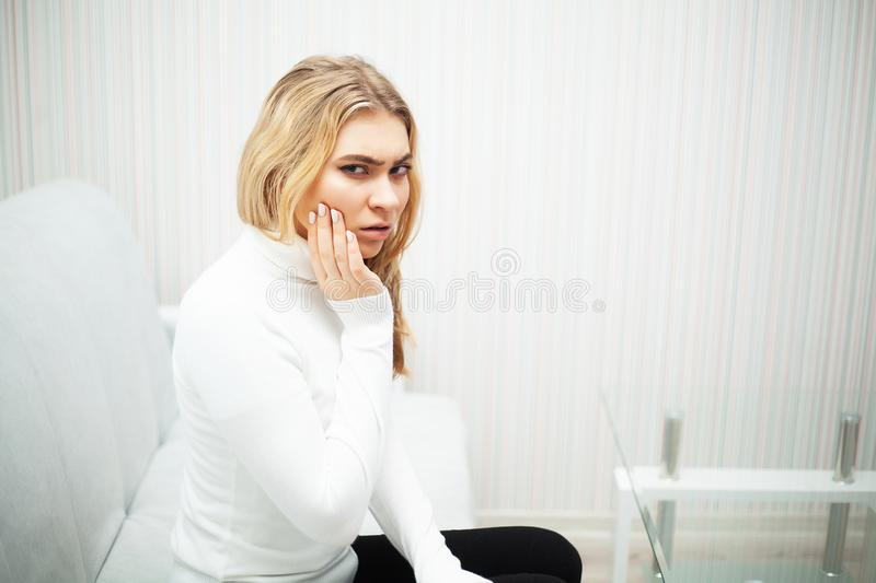 Pain. The problem of teeth. A woman feels pain in her tooth. A picture of a beautiful, sad girl suffering from severe royalty free stock photography