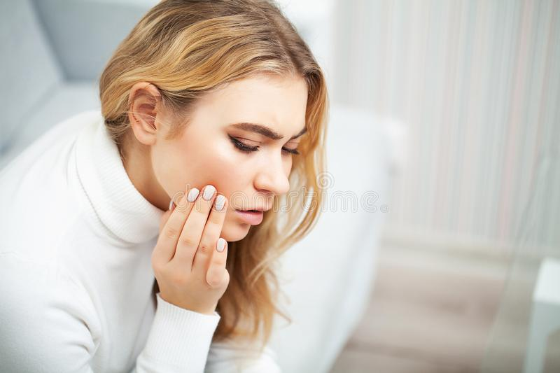 Pain. The problem of teeth. A woman feels pain in her tooth. A picture of a beautiful, sad girl suffering from severe stock photos