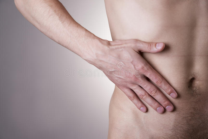 Pain in the right side. Attack of appendicitis. Man on a gray background royalty free stock image