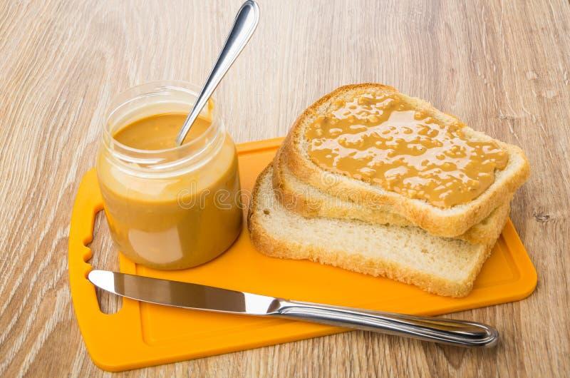 Pain, sandwich avec le beurre d'arachide, pot sur la planche à découper, couteau photo libre de droits