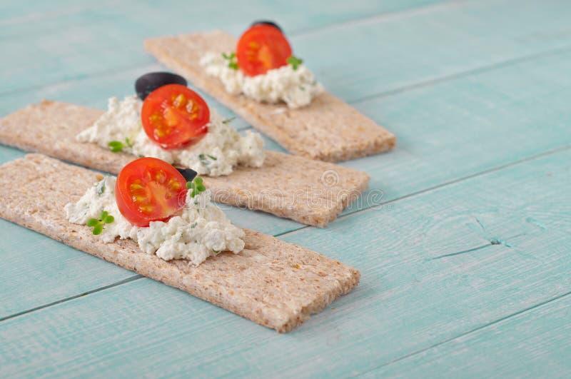 Pain sec avec le fromage blanc, les tomates-cerises et les olives noires images libres de droits