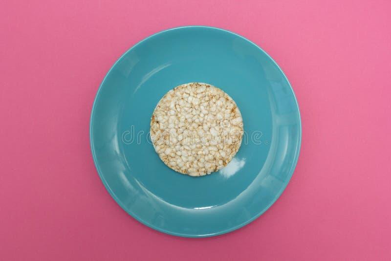 Pain v?g?tarien de riz d'un plat bleu sur un fond rose, vue sup?rieure R?gime photo stock
