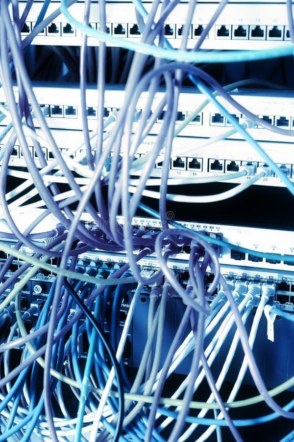 Painel da rede de um servidor da escola com cabo ethernet azul em interruptores, efect da cor imagens de stock