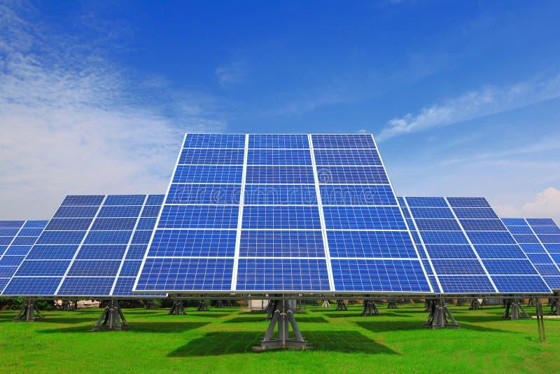 Painel solar com grama verde e o azul bonito SK fotografia de stock royalty free
