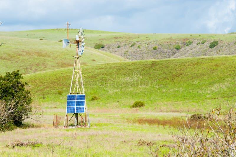 Painel solar das fontes de energia alternativas na justaposição do moinho de vento do vintage fotografia de stock royalty free