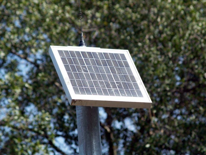 Painel solar pequeno no pólo com árvores imagens de stock royalty free