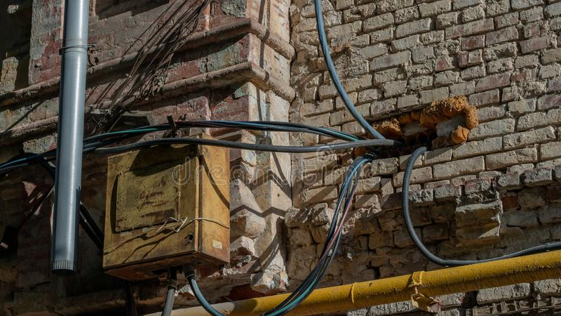 Painel velho do metal elétrico em uma parede do vermelho de tijolo Fios e tubulação amarela do gás para entrar na casa Violação d foto de stock royalty free