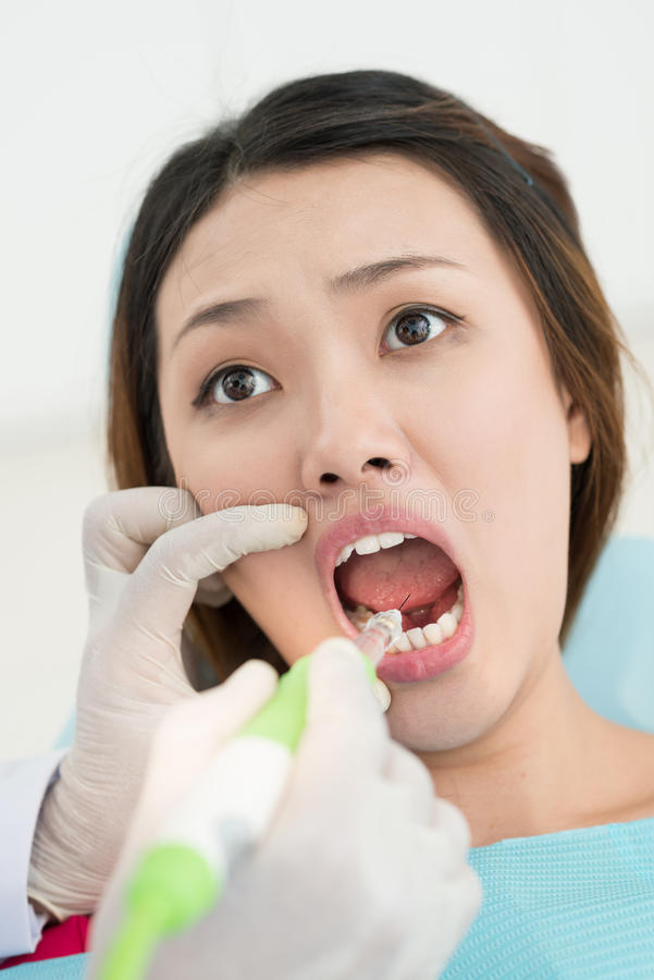 Painful dental procedure. Vertical image of a feared patient during the painful dental procedure royalty free stock photo