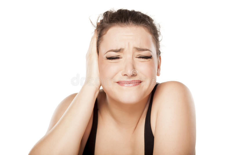 Painful ear. Unhappy young woman has pain in the ear royalty free stock image