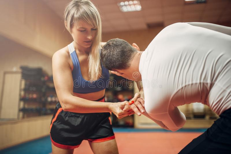 Painful grip of the hand, female self-defense. Female person makes painful grip of the hand, self-defense workout with male personal trainer, gym interior on stock photo
