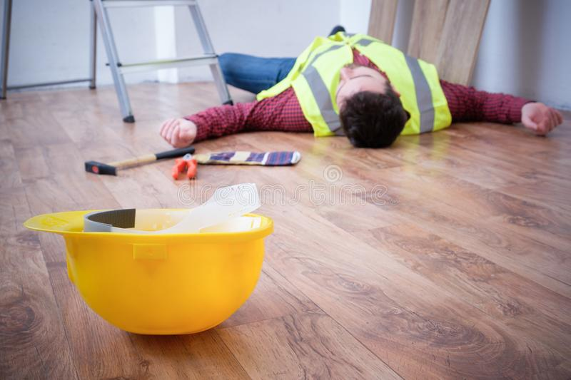 Painful worker after on the job injury. On the job injury of one worker fallen from a ladder stock images
