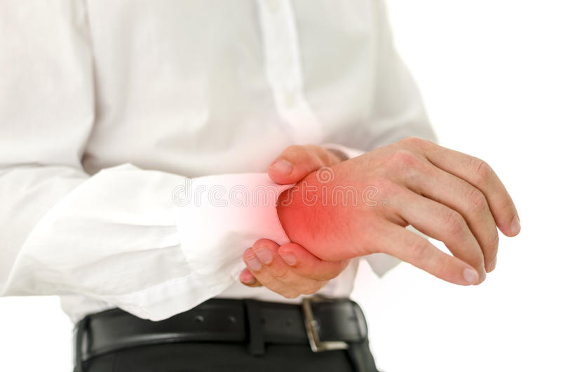 Painful wrist. Man holding his injured painful wrist. Red spot emphasizing hurt area royalty free stock photos