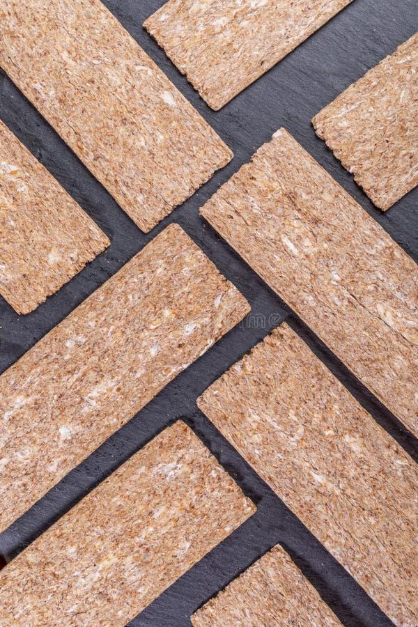Pains croustillants de maïs présentés dans le modèle géométrique diagonal sur le fond gris de schiste photo libre de droits