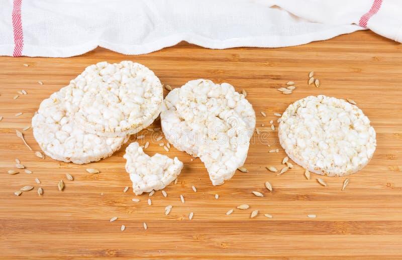 Pains croustillants de riz soufflé parmi des grains entiers sur la surface en bois images stock