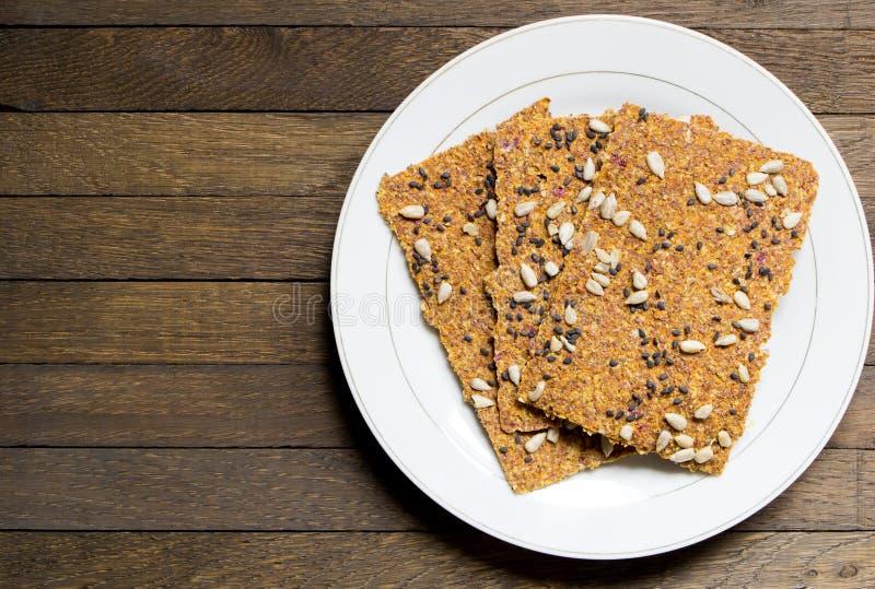 Pains crus de pain déshydratés par Vegan sur le plat blanc sur la table en bois photo libre de droits