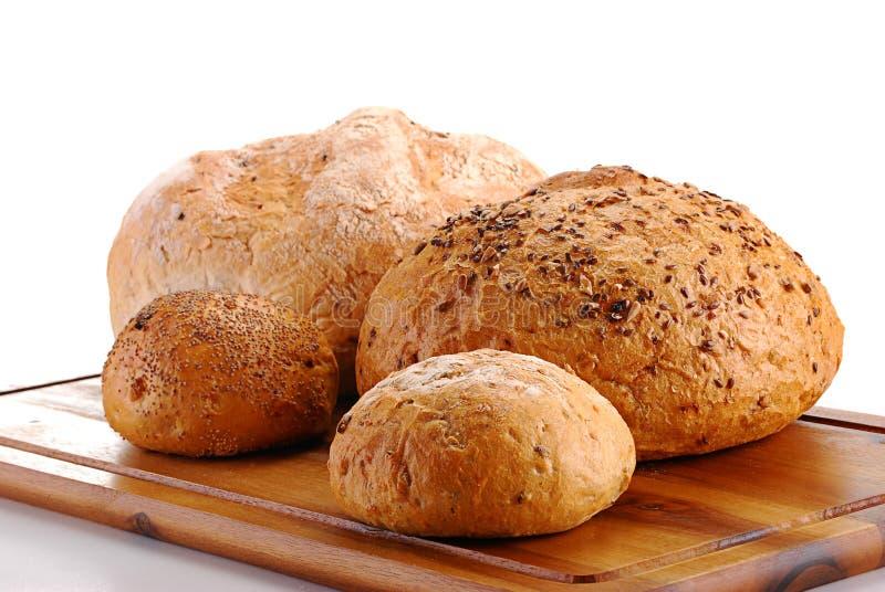 Pains de pain et des roulis sur la planche à pain images stock