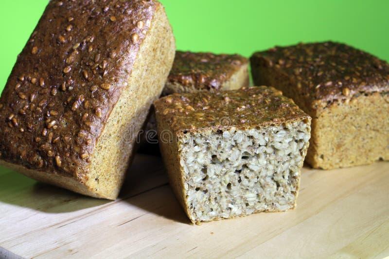 Pains entiers de grain sur le plateau, quatre pains foncés image stock