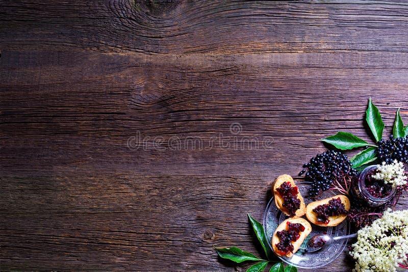 Pains grillés avec de la confiture de baie de sureau et les baies fraîches sur la table en bois L'espace libre pour votre texte images stock