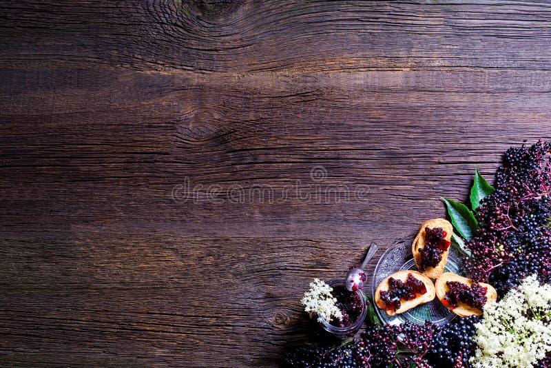 Pains grillés avec de la confiture de baie de sureau et les baies fraîches sur la table en bois L'espace libre pour votre texte image stock