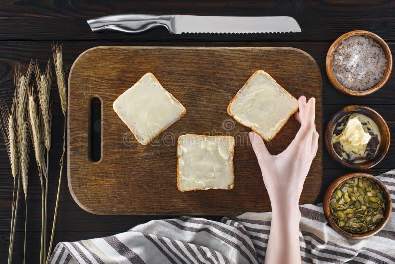 Pains grillés avec du beurre et la main humaine images stock